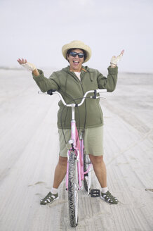 Senior woman with bicycle on beach - BLEF00036