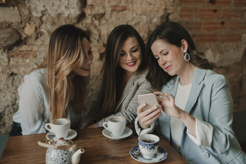 Three young women looking at cell phone in a cafe - AHSF00143