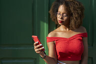 Woman in red checking her phone - VEGF00035