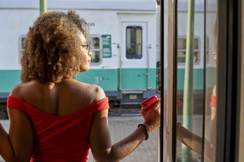 Woman looking out of train door - VEGF00038