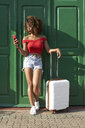 Woman in red with a suitcase checking her phone - VEGF00041