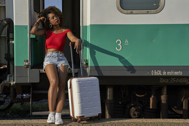 Woman with suitcase sitting at the door of a train - VEGF00047