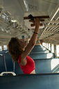 Young woman placing her suitcase in a train - VEGF00053