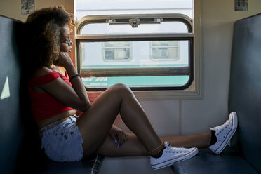 Young woman on a train looking out of window - VEGF00056
