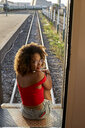 Woman sitting at the back door of a train turning round - VEGF00065