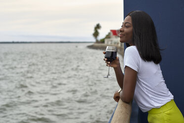 Happy young woman with glass of red wine looking at the sea - VEGF00074