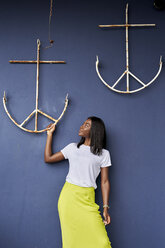 Young woman in front of blue background looking at anchor hanging at wall - VEGF00077