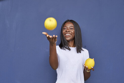 Portrait of happy young woman juggling with two oranges in front of blue background - VEGF00080