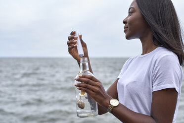 Profile of young woman in front of the sea sending message in a bottle - VEGF00083