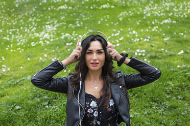 Portrait of young woman with white headphones, wearing black leather jacket - MGIF00386