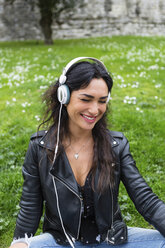 Portrait of young woman with white headphones, wearing black leather jacket - MGIF00389