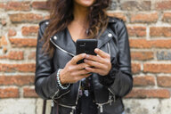 Young woman wearing black leather jacket, using smartphone, brick wall in the background - MGIF00392