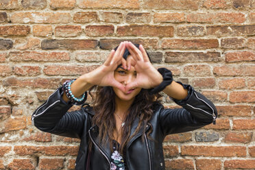 Portrait of young making heart shape with hands and fingers, brick wall - MGIF00395