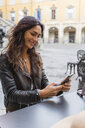 Young woman with cup of coffee, using smartphone - MGIF00398
