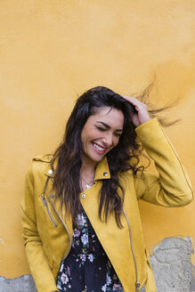 Portrait of young laughing woman wearing yellow leather jacket, hand in hair - MGIF00401
