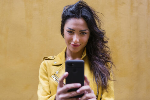 Portrait of young woman wearing yellow leather jacket and taking a selfie, yellow wall in the background - MGIF00404