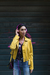 Portrait of young woman with pink headphones, wearing yellow leather jacket - MGIF00407