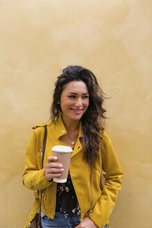 Portrait of young woman wearing yellow leather jacket, holding cup of coffee - MGIF00410