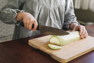 Girl's hands slicing courgette, partial view - EYAF00173