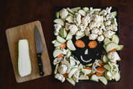 Funny face made of sliced vegetables on baking tray - EYAF00179