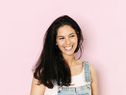 Portrait of young smiling woman with black hair in front of pink background - HMEF00349