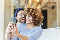 Laughing couple taking a selfie - FMKF05616