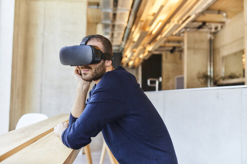 Young man wearing VR glasses in modern office - FMKF05625