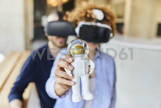 Man and woman wearing VR glasses holding astronaut figurine - FMKF05628 - Jo Kirchherr/Westend61