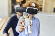 Man and woman wearing VR glasses holding astronaut figurine - FMKF05628