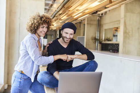 Happy man and woman with laptop fist bumping in modern office - FMKF05634