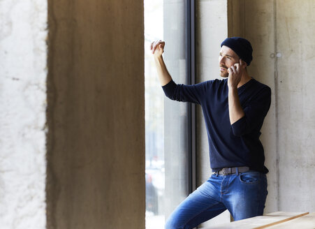 Young man on the phone looking out of window - FMKF05643