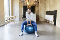 Portrait of young man sitting on fitness ball in modern office - FMKF05646