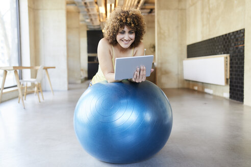 Smiling woman using tablet on fitness ball in modern office - FMKF05649