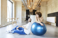 Smiling man and woman with fitness ball in modern office - FMKF05652