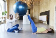 Happy man and woman practicing with fitness ball in modern office - FMKF05655
