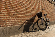 Denmark, Copenhagen, bicycle leaning against brick wall at sunlight - AFVF02730