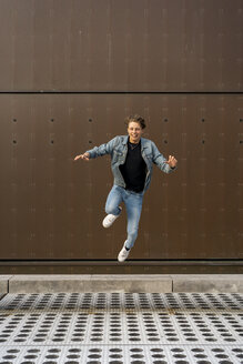 Young man jumping in front of a wall - AFVF02774