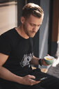 Young man drinking coffee and using mobile phone in coffee shop - OCMF00426