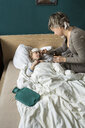 Mother giving medicine to sick daughter lying in bed - PSIF00254
