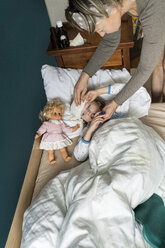 Mother taking temperature of sick daughter lying in bed - PSIF00257