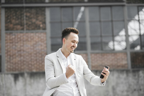 Portrait of smiling businessman with smartphone - KMKF00865