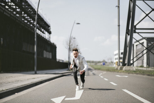 Businessman in starting position on a road with arrow - KMKF00868