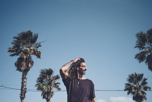 Man posing among palm trees - OCMF00430