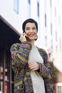 Spain, Madrid, Madrid. Young woman with very short haircut, using smartphone outdoors. Lifestyle concept. - JSMF00964