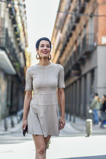 Spain, Madrid, Madrid. Happy woman, with very short haircut, wearing dress and smiling in urban background. Lifestyle concept. - JSMF00970
