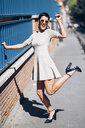 Happy fashionable young woman wearing dress and sunglasses - JSMF00973