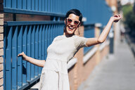 Happy fashionable young woman wearing dress and sunglasses - JSMF00976