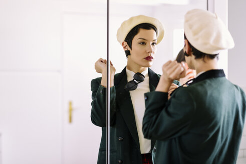 Spain, Madrid, Madrid. Woman with very short hair giving the last touches of makeup in front of the mirror. Lifestyle concept. - JSMF00988