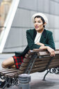 Fashionable young woman sitting on a bench - JSMF00997