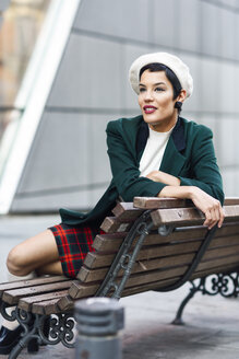 Spain, Madrid, Madrid. Modern woman, wearing green jacket, checked skirt and white beret, sitting on a bench in the street. Lifestyle concept. - JSMF00997